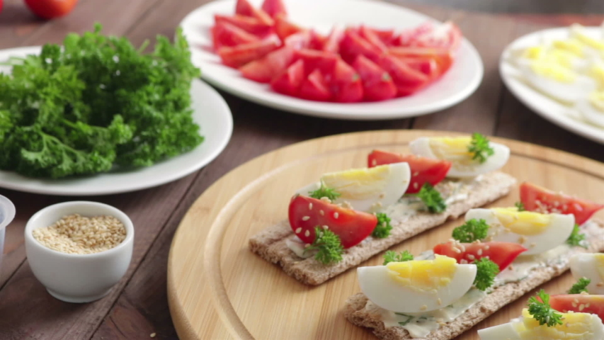 Healthy sandwiches with crispbread boiled egg tomato cream cheese  on cutting board panning shot   Shutterstock HD Video #1046540212