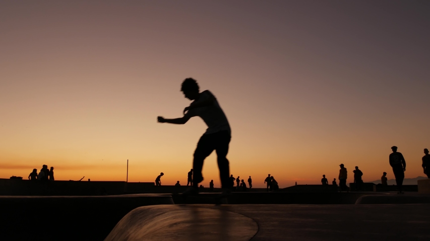 Silhouette of young jumping skateboarder riding longboard, summer sunset background. Venice Ocean Beach skatepark, Los Angeles California. Teens on skateboard ramp, extreme park. Group of teenagers