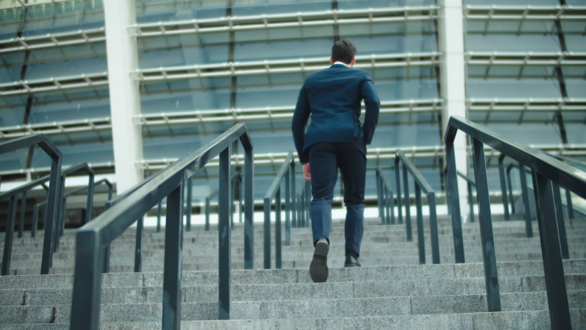 Back view stylish business man going upstairs in suit at street. Successful businessman walking at stairs alone outdoors. Young man walking in luxury suit near stadium.
