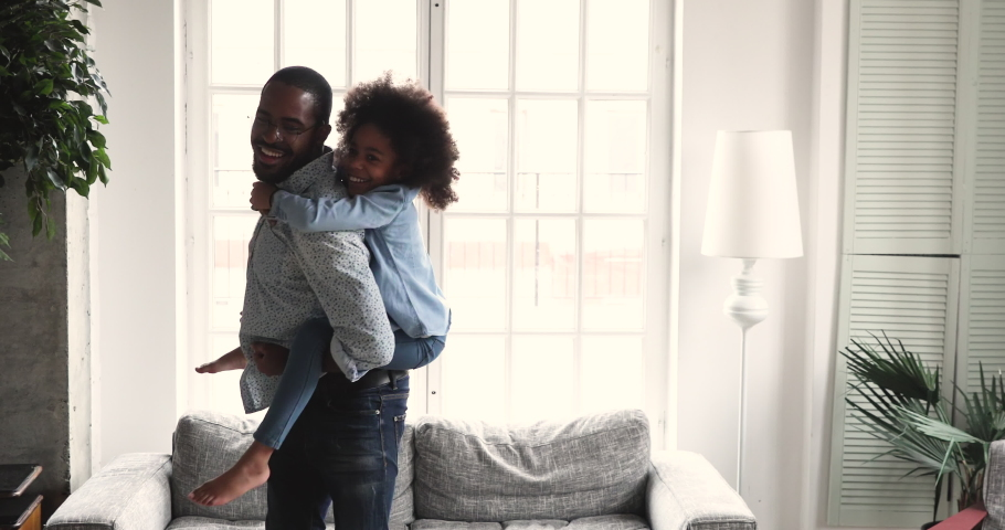 Happy african dad carrying preschool kid daughter give piggyback ride at home, loving young adult afro american father play funny active game with small child girl having fun laughing in living room