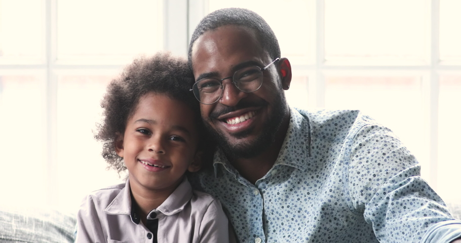 Cheerful smiling african american young adult father and little cute kid son looking at camera laughing at home, mixed race family dad child boy happy faces sit on sofa bonding, closeup portrait