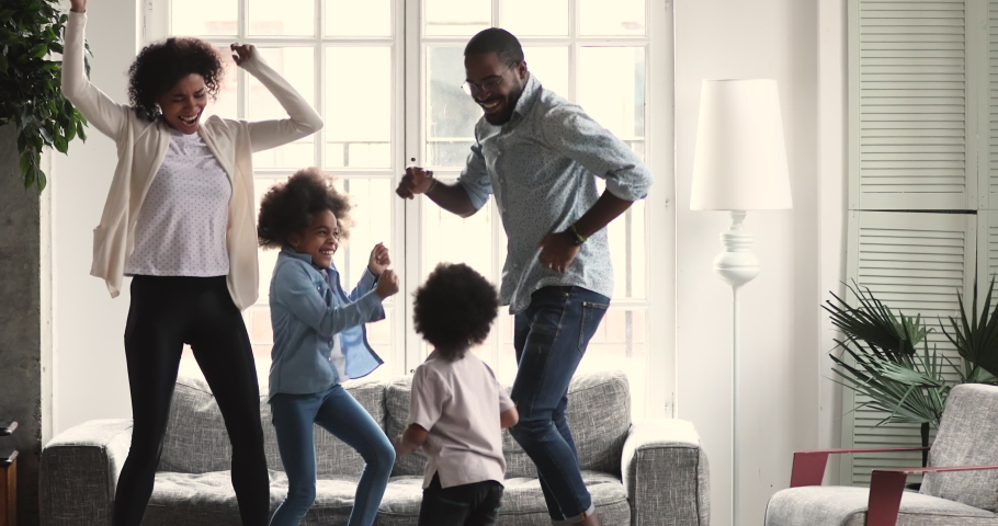 Happy carefree african american ethnic couple dancing with cute active preschool small children in living room interior together, family mortgage and parents with kids weekend fun at home concept Royalty-Free Stock Footage #1046570437