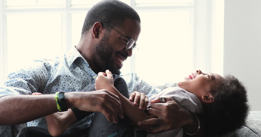 Affectionate african family young adult father tickling little adorable child son having fun laughing relaxing on sofa, afro american dad playing with small kid boy bonding cuddling together at home