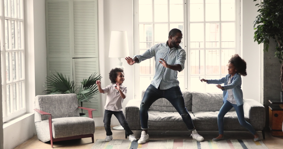 Happy active african american dad teaching dancing having fun with two cute small kids son and daughter imitate father moves playing together enjoying funny weekend activity in modern living room