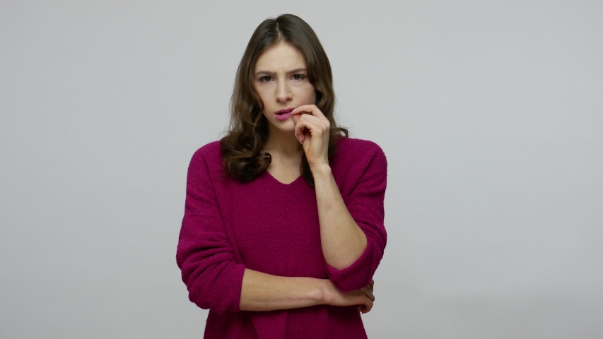 Confused thoughtful brunette woman in pullover biting lips from anxiety while pondering with perplexed expression, looking puzzled worried, having doubts. studio shot isolated on gray background Royalty-Free Stock Footage #1046578972