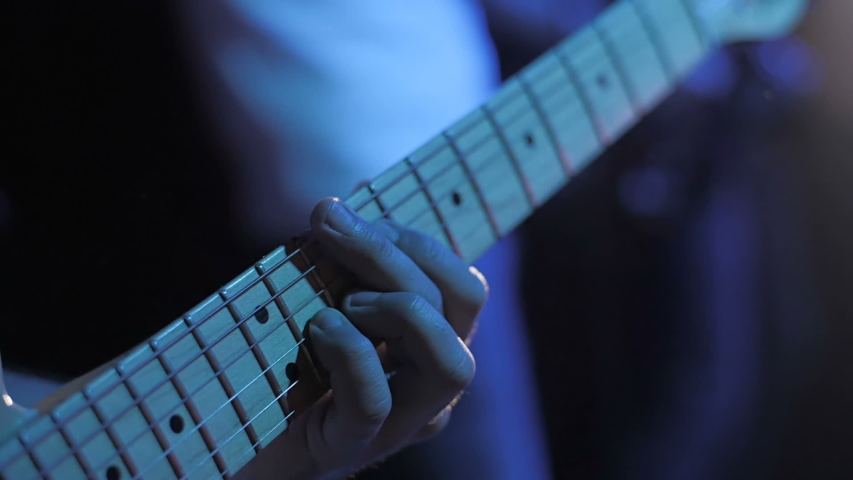 Guitarist performs on stage. Performing in slow motion. Closeup guitar view. Metal concert. Rock gig. Guitar strings. Rock music band. Music player. Electric guitar. Young music artist. Grunge concert | Shutterstock HD Video #1046579308