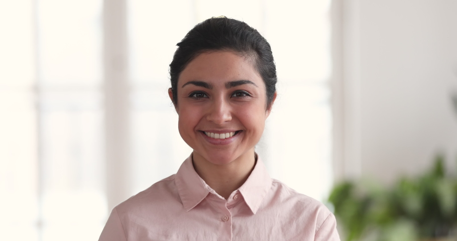 Close up portrait of smiling millennial indian ethnic business woman entrepreneur posing in corporate office, happy confident young adult beautiful female professional leader executive look at camera