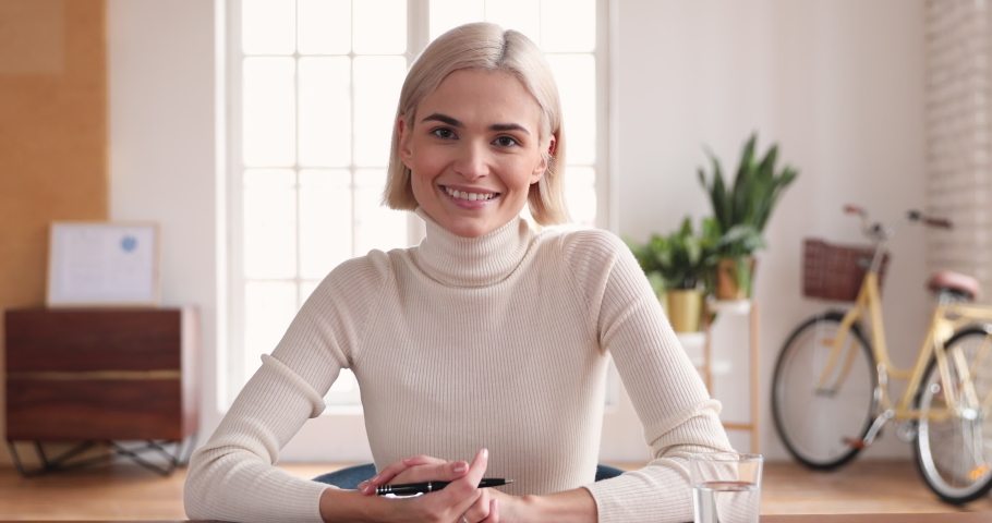 Young professional businesswoman talking to camera sit at office desk making corporate conference call, female manager speaking looking at webcam doing online video chat presentation, web cam view