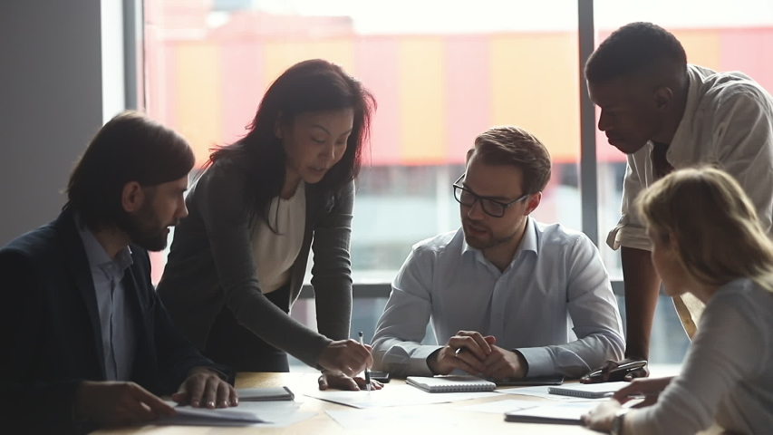 Motivated middle aged asian female team leader explaining company development strategy to smiling young diverse colleagues. Happy multiracial business people enjoying working together at office. | Shutterstock HD Video #1046595526