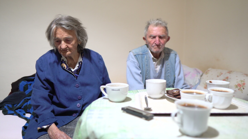 Senior couple with dementia drinking coffee on the couch in the living room. | Shutterstock HD Video #1046600440