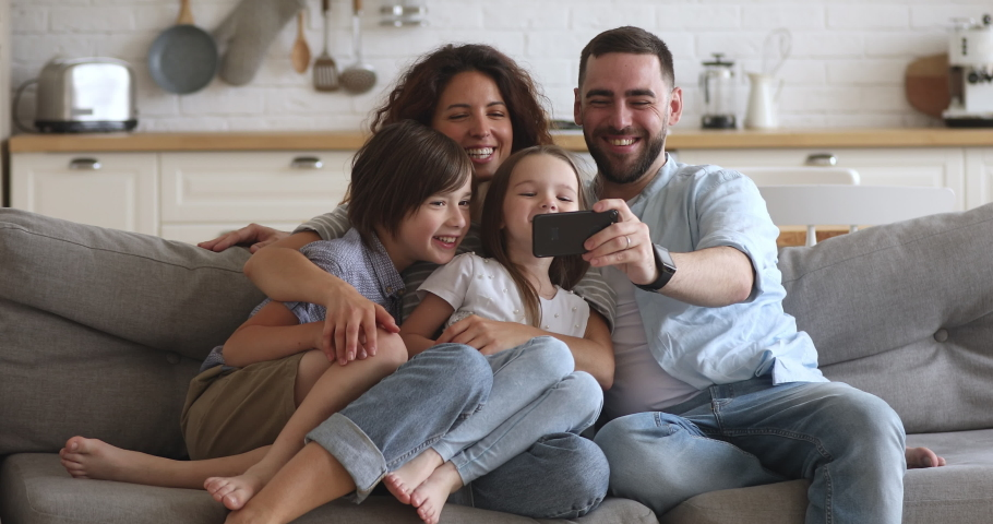 Happy bonding family of four sitting on couch, smiling father holding mobile phone, taking selfie. Excited couple posing for photo with children siblings or holding online call with grandparents.