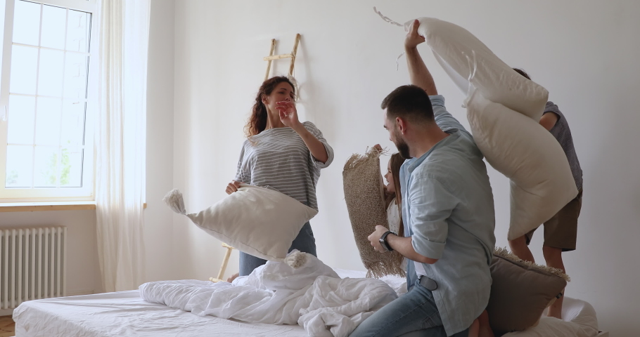 Joyful married couple fighting pillows with happy little children siblings in bedroom. Overjoyed family of four having fun, playing with small kids, enjoying weekend leisure time together at home. | Shutterstock HD Video #1046602045