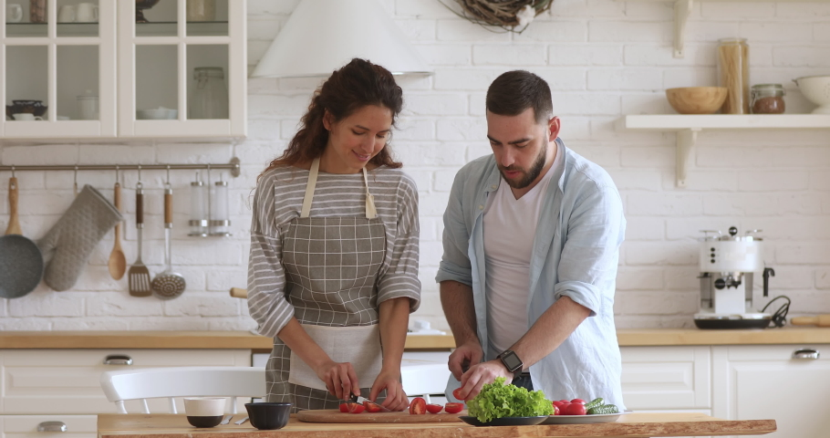 Happy attractive woman feeding husband while cooking together at modern kitchen. Smiling family couple laughing, enjoying preparing healthy vegetarian food salad meal for romantic dinner at home. Royalty-Free Stock Footage #1046602051
