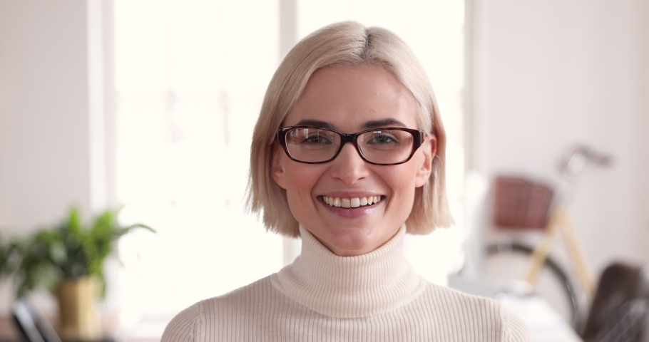Smiling confident young adult blonde businesswoman manager professional wear glasses looking at camera in corporate office, happy smart millennial female model worker manager close up face portrait