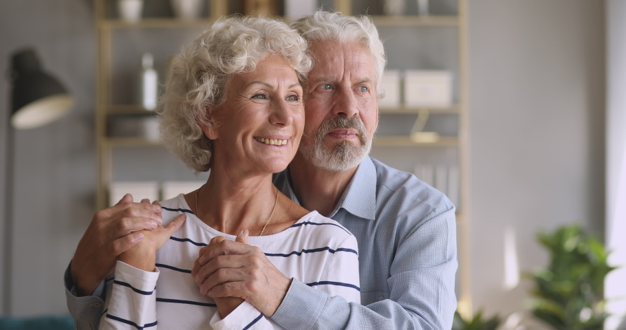 Happy mature man husband embracing smiling middle aged wife, looking at camera. Bonding attractive older senior family couple looking away, dreaming of future, planning retirement together at home. Royalty-Free Stock Footage #1046611573