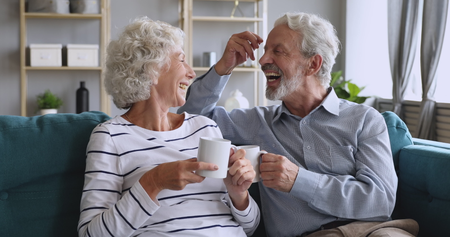 Affectionate mature family couple relaxing on cozy sofa, enjoying pleasant conversation, holding cups of hot tea. Loving happy middle aged man joking talking discussing with elderly smiling wife.