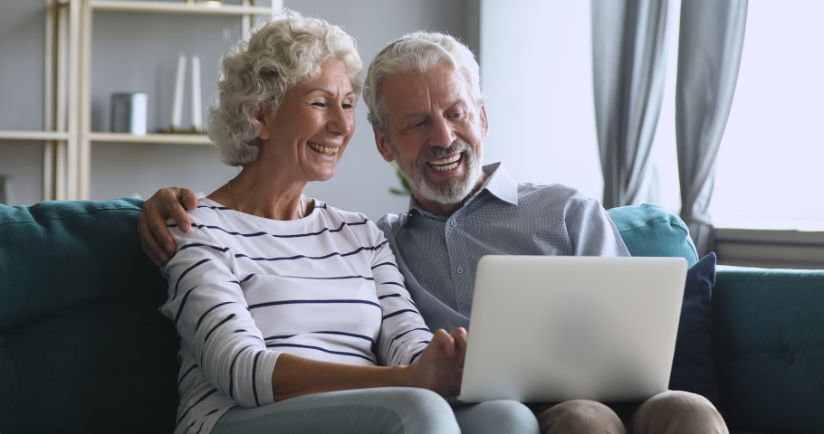 Serious middle aged man cuddling smiling hoary wife, explaining new computer software, sitting together at home. Happy older family couple discussing media news, relaxing together in living room.