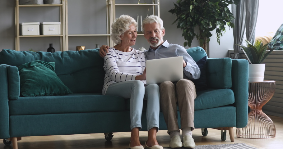 Full length happy older family couple relaxing on comfortable couch at home, using computer. Smiling middle aged married retired spouses web surfing, discussing news, shopping online together.