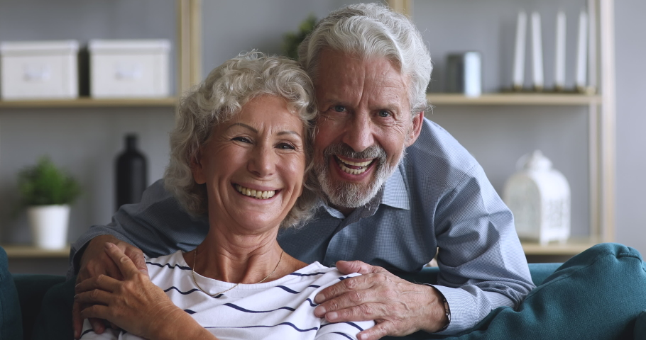 Head shot video portrait loving elderly husband embracing sitting on couch smiling hoary woman, looking at camera. Happy married couple posing for family portrait, enjoying tender moment together.