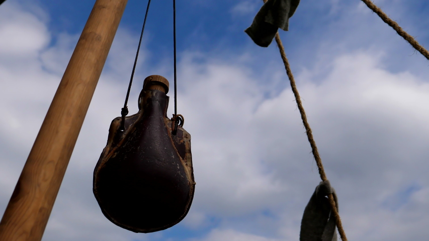 Old leather bottle or water skin swinging against sky at viking reenactment camp.