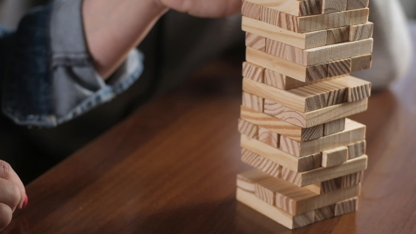 boy and his mother play jenga. Educational Board games for family.  Close-up of the game with dice at home. The family have fun playing with wooden blocks. children and parents play at home together. Royalty-Free Stock Footage #1046635867