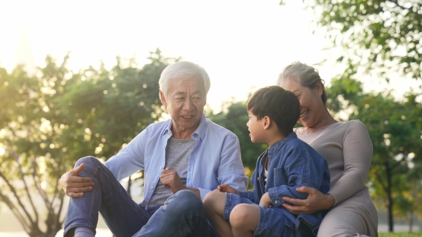 Asian grandparents sitting outdoors on grass talking having fun with grandson