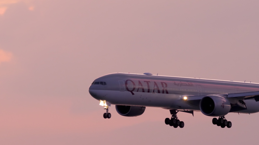 PHUKET, THAILAND - NOVEMBER 28, 2019: Qatar Airways Boeing 777 approaching before landing on the Phuket airport against sunset sky. View from the top floor of the hotel near airport