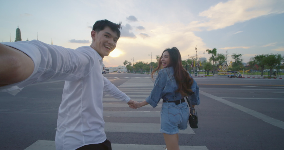 Sweet couple have romantic time while honeymoon trip in Bangkok city Thailand. POV of Young Asian couple holding hands and taking selfie while running and crossing the street in slow motion.  | Shutterstock HD Video #1046642995