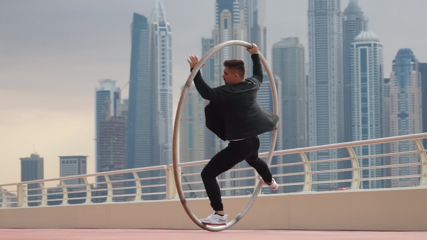 Cyr Wheel artist doing tricks slow motion wearing black and white smart clothes with cityscape background of Dubai during sunset | Shutterstock HD Video #1046646514