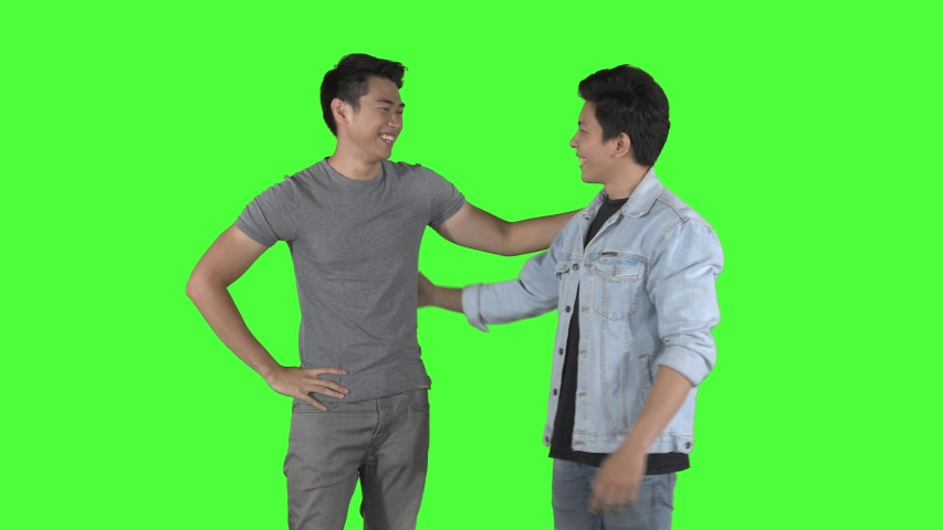 Two young man meeting and hugging each other while chatting in the studio. Shot in 4k resolution with green screen background