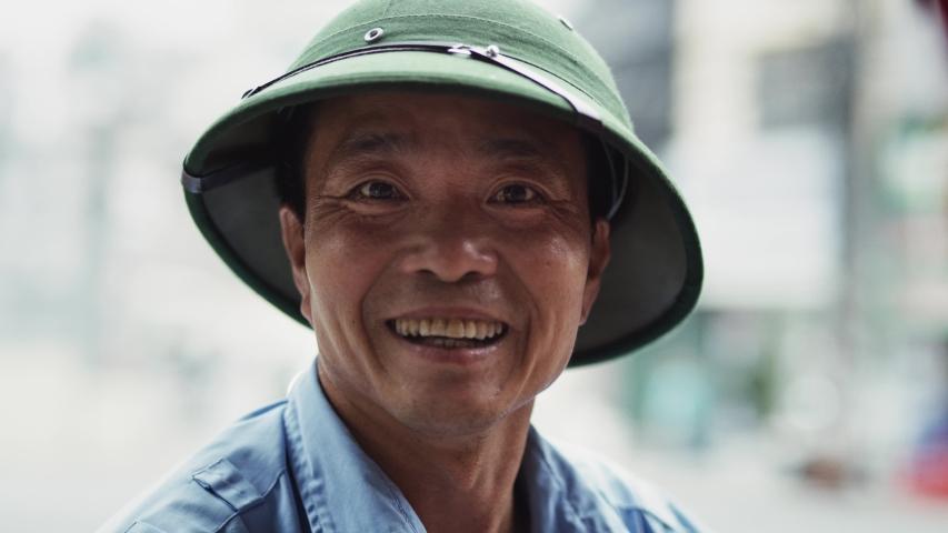 Handheld video shows of Vietnamese mature man looking at camera.   Royalty-Free Stock Footage #1046668387