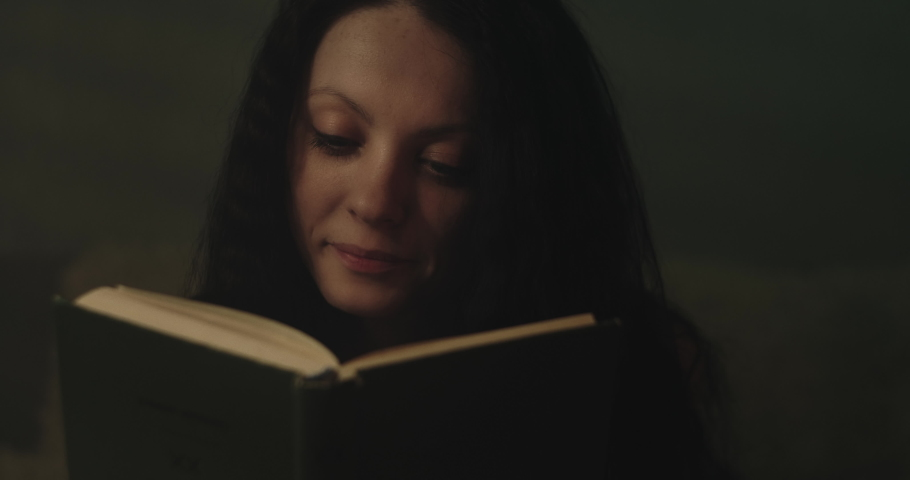 Young woman reading a book in a dimly lit room. Close-up.