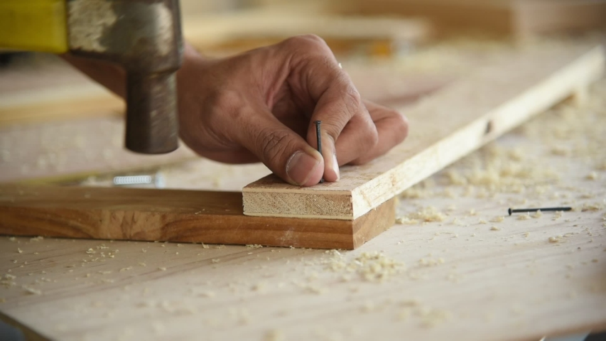 Close up man worker using hammer to nail wood plank for build diy wood furniture in workshop
