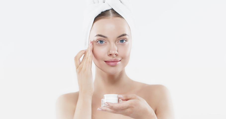 Beauty portrait of beautiful woman applying face cream isolated on white background. Female skin care concept. Focus on cream | Shutterstock HD Video #1046669188