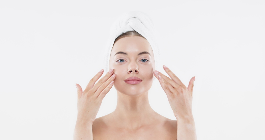Young woman with blue eyes applying serum to her face, looking at camera, isolated on white background. Beautiful model girl with perfect clean fresh skin. Skin care treatment or cosmetic ads concept | Shutterstock HD Video #1046669197
