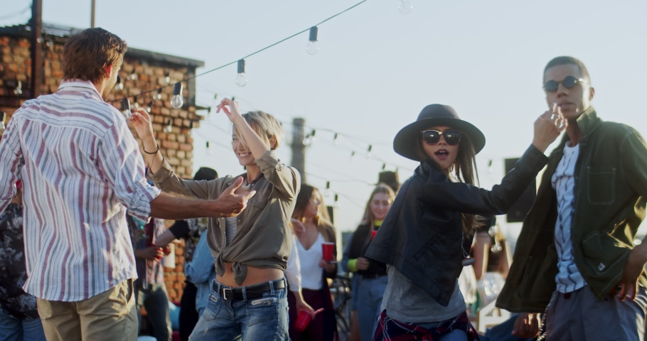 Young mixed-races men and women dancing cheerfully at the celebration of big holiday on the rooftop during a party. Outdoors.   Shutterstock HD Video #1046673193