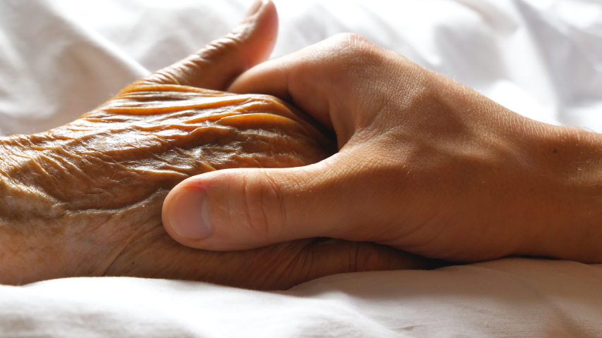 Worried man taking and gently stroking hand of his sick mother showing care or love. Son comforting wrinkled arm of elderly mom lying at bed. Guy giving support to his old parent. Side view Close up