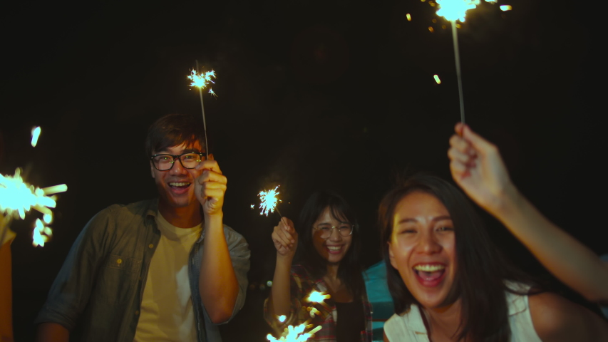 4K UHD Slow motion : Group of asian friend having fun cekebrates with sparklers lights in camping on summer beach at night. Everybody are happy dancing, outdoor activity or holiday vacation.