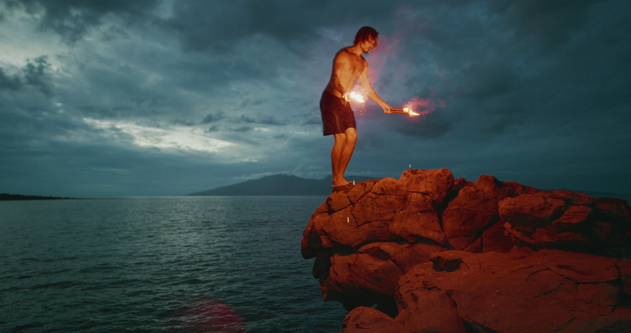 Extreme cliff jumping man backflipping off of an sea cliff with burning red hot flares, epic stuntman moments, people are awesome | Shutterstock HD Video #1046706850