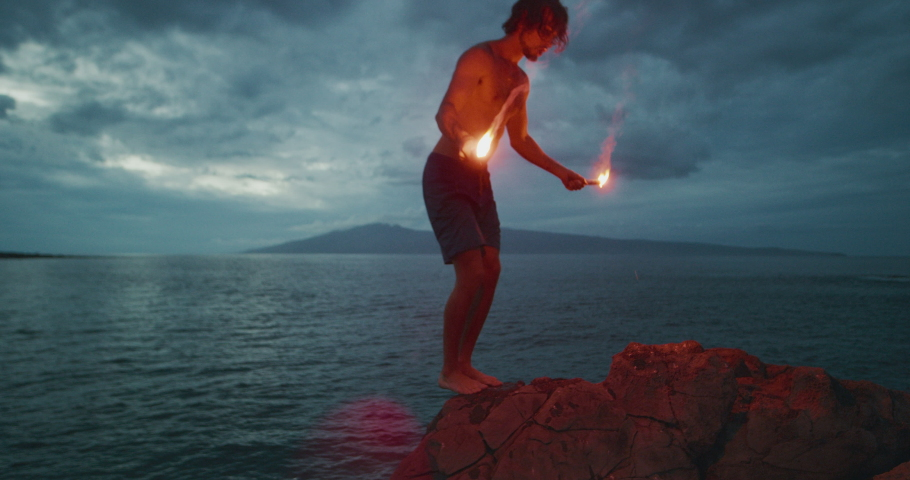 Extreme sports stunt man backflipping off of a sea cliff into the ocean with burning hot red flares, radical cliff jumping athlete, people being awesome | Shutterstock HD Video #1046707033