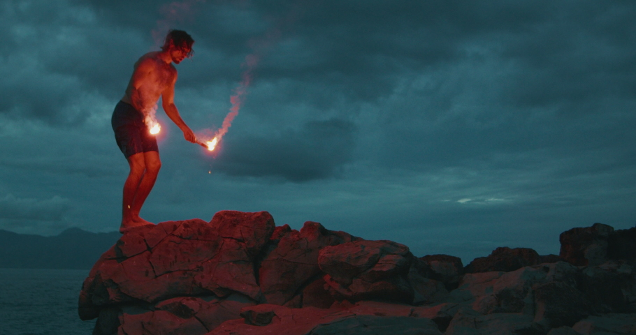 Extreme sports stunt man backflipping off of a sea cliff into the ocean with burning hot red flares, radical stuntman moments, people being awesome Royalty-Free Stock Footage #1046707039