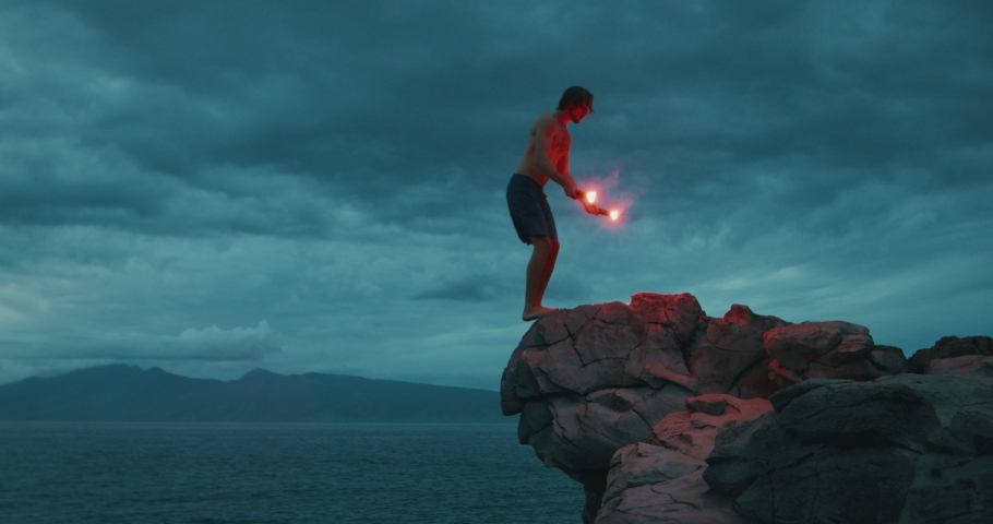 Extreme sports cliff diver doing a backflip off of a sea cliff with burning red flares, epic video of people being awesome, backflips with fireworks   Shutterstock HD Video #1046707042