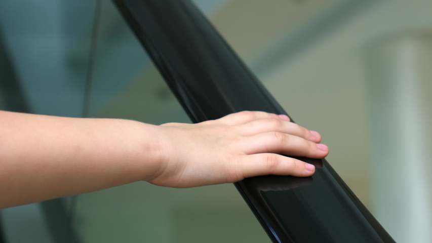 The girl's hand on the handrail of the escalator. close up | Shutterstock HD Video #1046714659