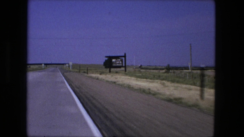 FORT WAYNE INDIANA-1976: Driving Along A Road With Massive Fields On Both Sides Of The Road And A Road Sign