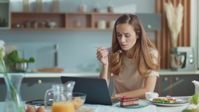 Businesswoman working on laptop computer at home office. Portrait of thoughtful girl eating cake on domestic kitchen. Pretty business woman using laptop on kitchen in slow motion