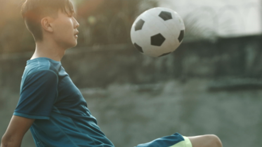 Young Korean guy with blue jersey practicing soccer skills and tricks with the ball at sunset in an outdoor urban spot with grungy walls Royalty-Free Stock Footage #1046730295