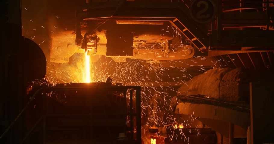 A furnace in which metal is melted. Sparks and smoke from the fire. Metallurgical industry. Car engine factory | Shutterstock HD Video #1046754247