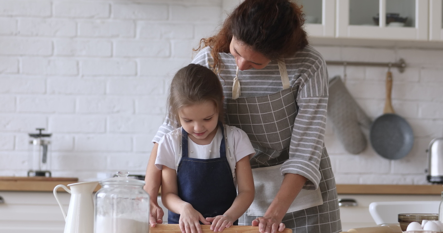 Happy young mommy helping little preschool daughter using rolling pin, preparing dough for homemade pastry together in modern kitchen. Smiling small kid girl enjoying cooking baking with mom. | Shutterstock HD Video #1046766055
