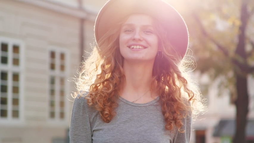 Beautiful Young Woman with long Curly Hair having a Pleasant walk in the City Center. Looking Pretty and gorgeous. Having lovely Smile. Nice Eyes and rose cheeks. Having trendy Hat on her Head.