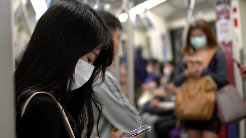 Asian woman wearing protective mask against transmissible infectious diseases and as protection against pollution and the flu in subway, Bangkok, Thailand. Royalty-Free Stock Footage #1046772631